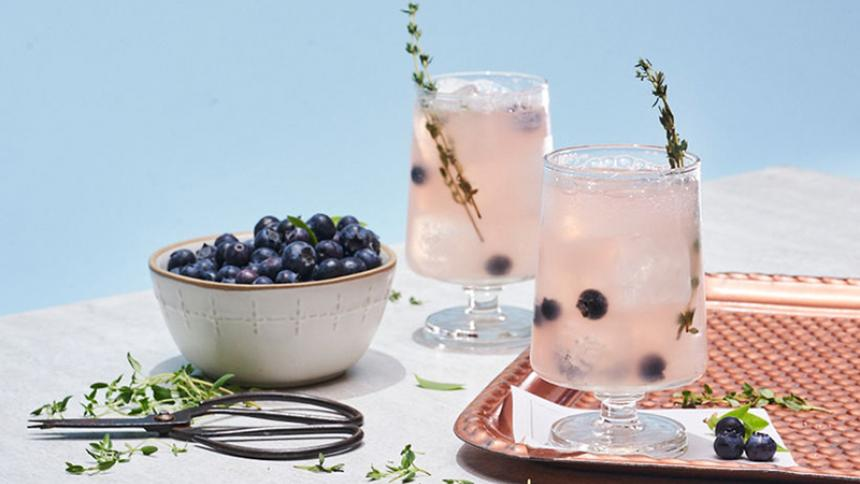 Two cocktails and a bowl of blueberries